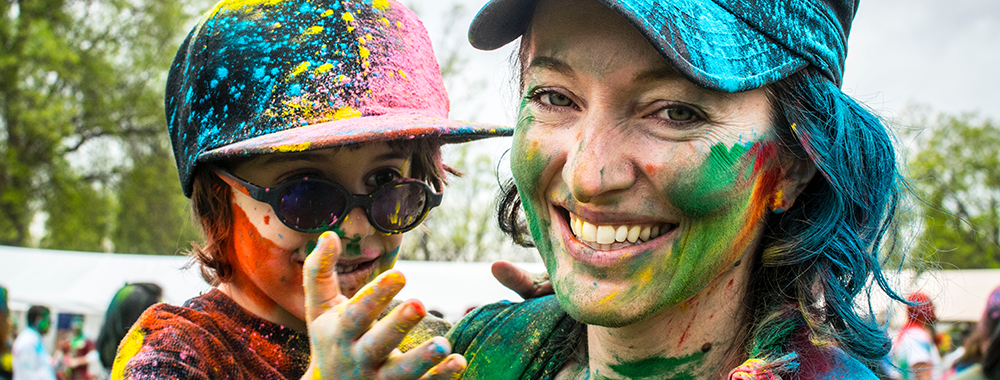 mother and son smiling and covered in colorful paint