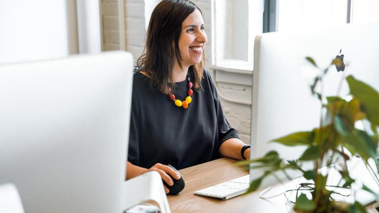 women smiling while sitting behind her computer working