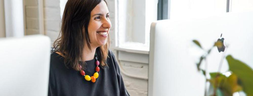 woman working at her desk and smiling