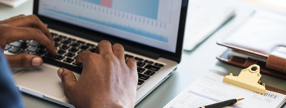 photo of hands using a laptop to view a financial related graphic
