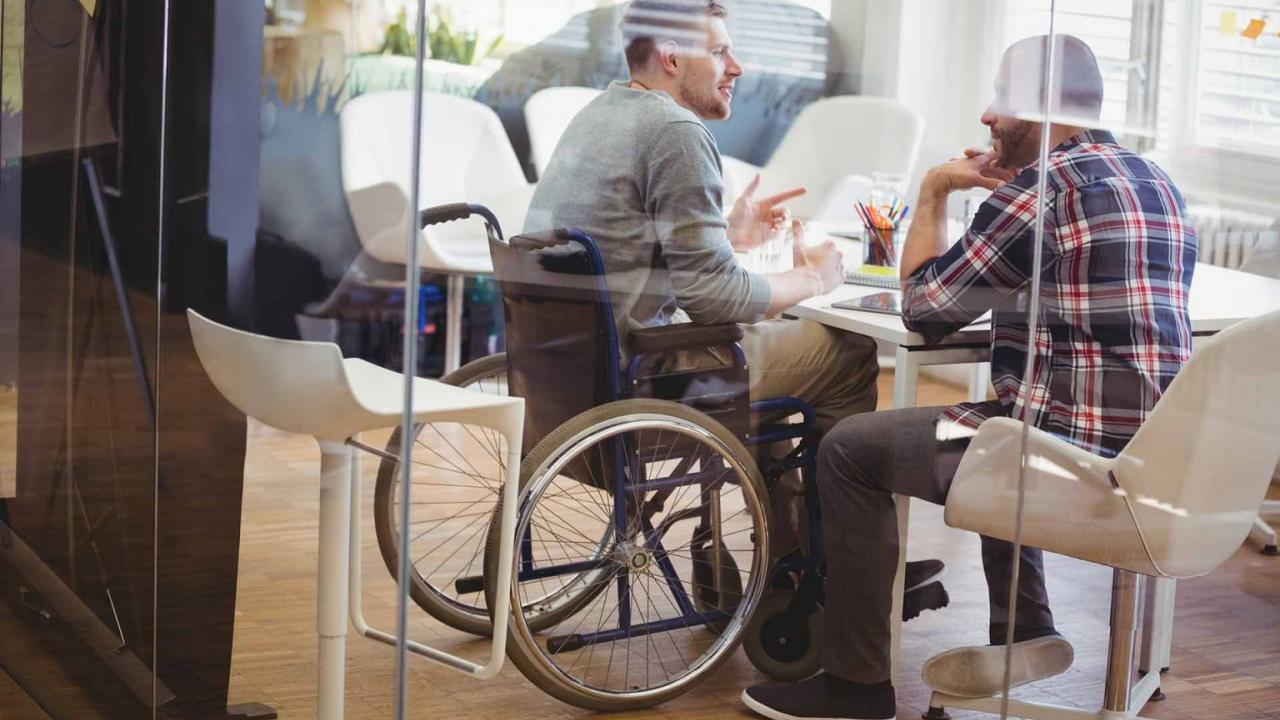Person in wheelchair at a desk talking to someone else.