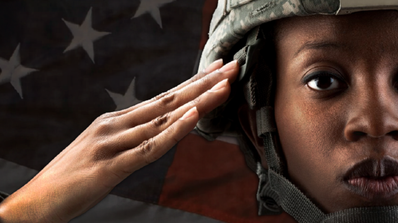 female soldier saluting in front of an american flag