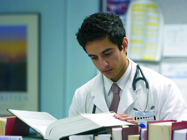 doctor reading from a textbook