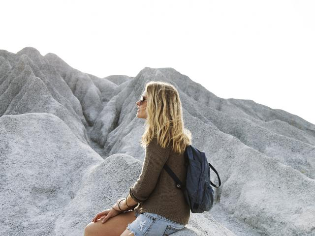 young woman sitting alone on a rock looking into the distance