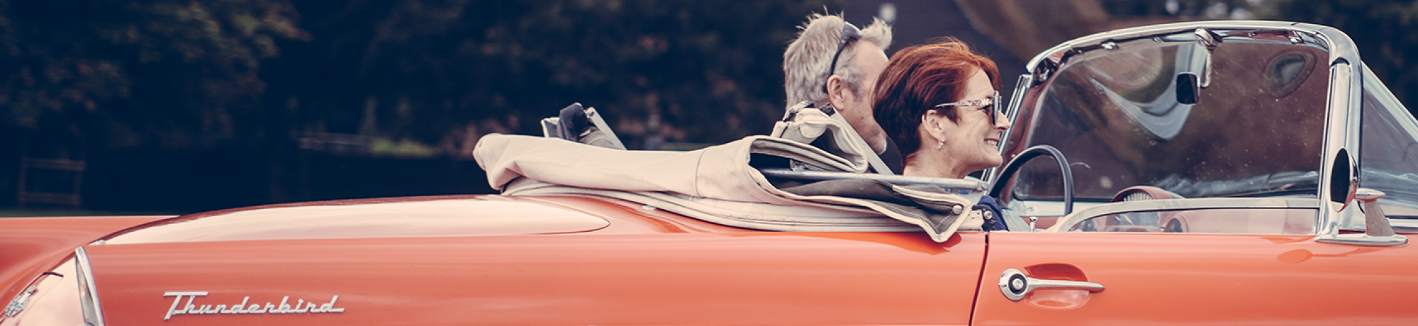 an older couple in a red convertible