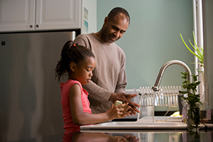 daughter and father washing dishes together