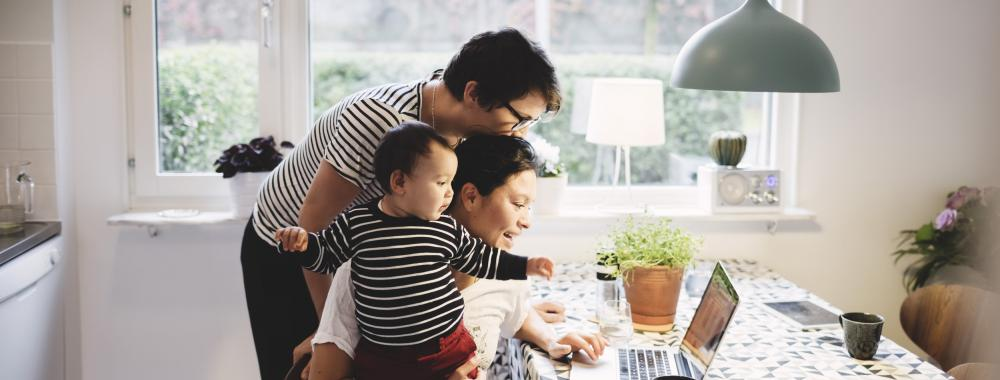 family looking at computer screen. One is holding a baby.