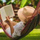 person in hammock reading book and relaxing.